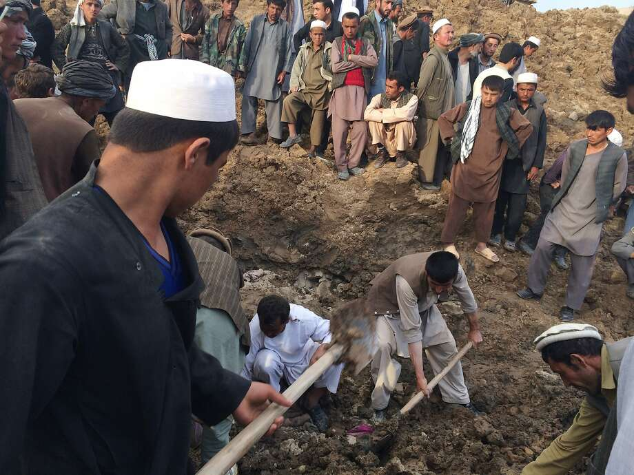 In this Friday, May 2, 2014 photo provided by Homayoon Rahmani, chief of road reconstruction program in the Afghan Rural and Rehabilitation Development Ministry, Afghans search for survivors buried after a massive landslide in a village in Badakhshan province, northeastern Afghanistan. Afghan rescuers and hundreds of volunteers armed with shovels rushed on Saturday to help villagers hit by a massive landslide in the remote northeast a day earlier, officials said, while fears of a new torrent of mud and earth complicated rescue efforts. (AP Photo/Homayoon Rahmani) Photo: Homayoon Rahmani, Associated Press