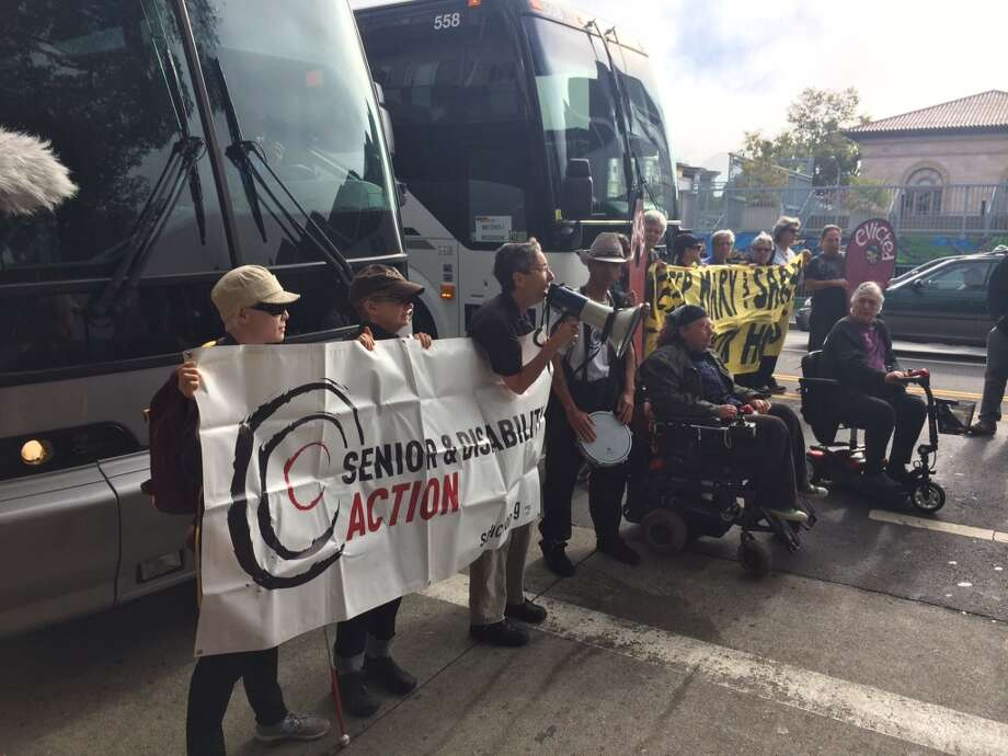 A group of seniors and people with disabilities, protesting against the tech industry and its workers, block two shuttle buses picking up tech employees at 24th and Valencia streets in San Francisco on Friday. Photo: Kristen V. Brown, The Chronicle