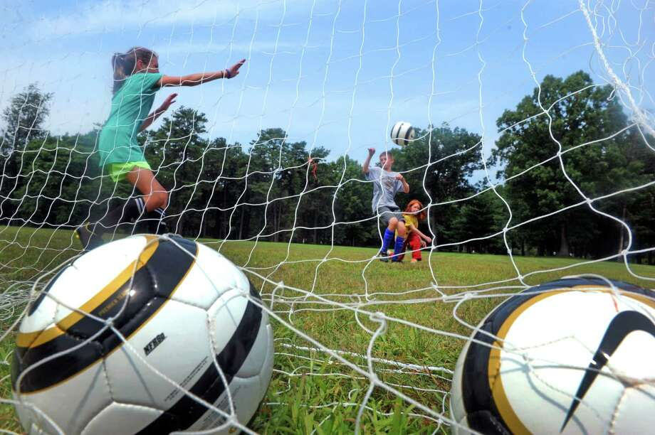 Ten-year-old Gwen Breshears, left, plays goal during a kids soccer camp sponsored by Nike Soccer and taught by brothers Mike and Jake Boland at Cook Park on Friday Aug. 1, 2014 in Colonie, N.Y. (Michael P. Farrell/Times Union) Photo: Michael P. Farrell / 00028012A