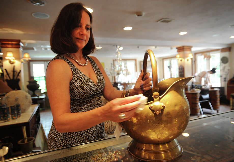 Owner Dottie DeLuca polishes a English brass coal scuttle at Fleur De Lis Antiques and Design at 4 Long Ridge Road in West Redding, Conn., on Thursday, July 24, 2014. Photo: Brian A. Pounds / Connecticut Post