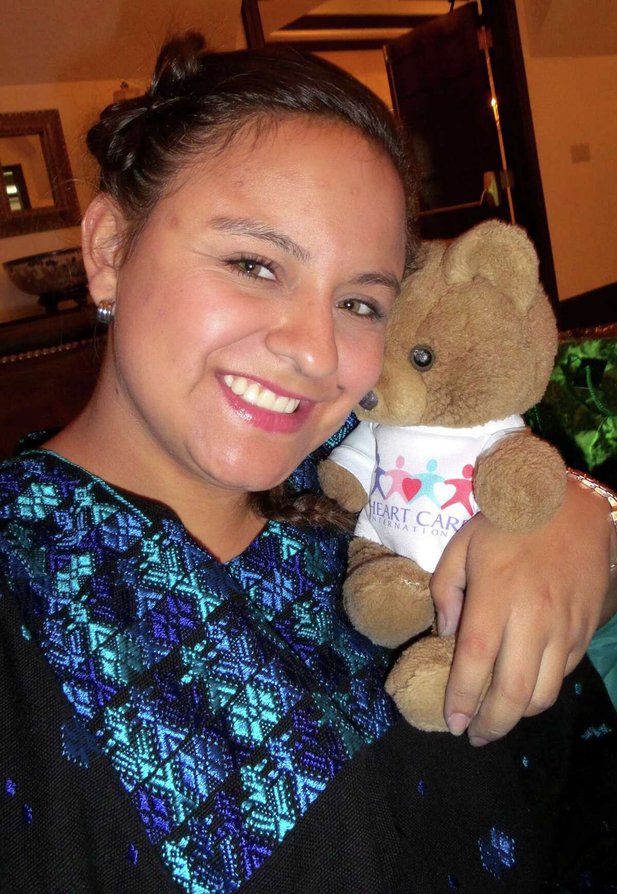Claudia Maria Sarai Tujab hugs her teddy bear given to her at the the time of her heart surgery 19 years ago by a Heart Care International (HCI) medical team. Tujab says her teddy bear has been adopted by her little sister Melanie.