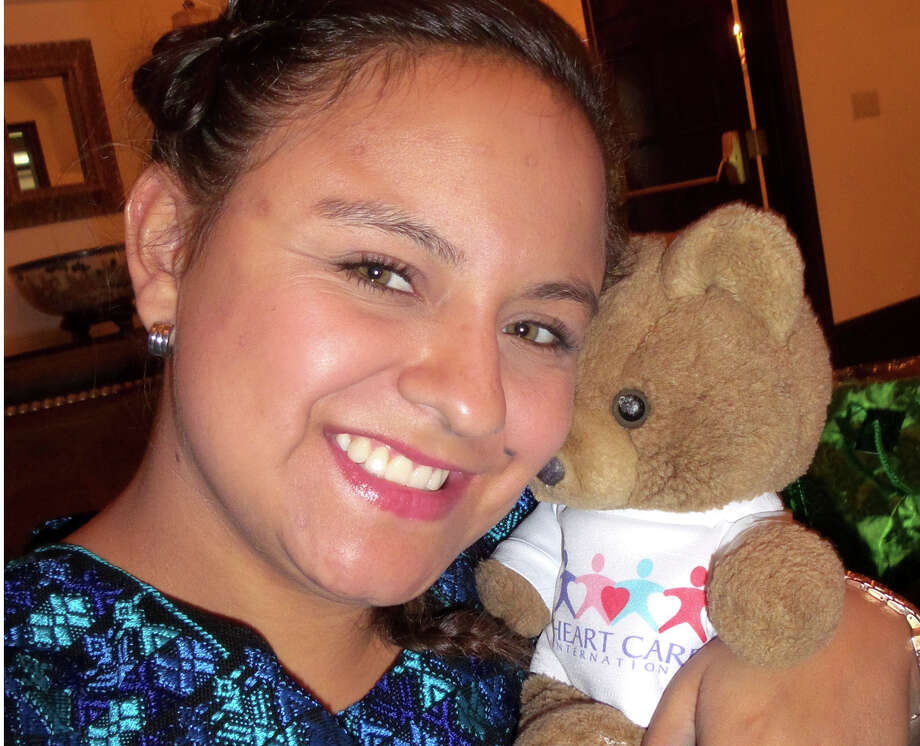 Claudia Maria Sarai Tujab hugs her teddy bear given to her at the the time of her heart surgery 19 years ago by a Heart Care International (HCI) medical team. Tujab says her teddy bear has been adopted by her little sister Melanie. Photo: Contributed Photo / Greenwich Time Contributed
