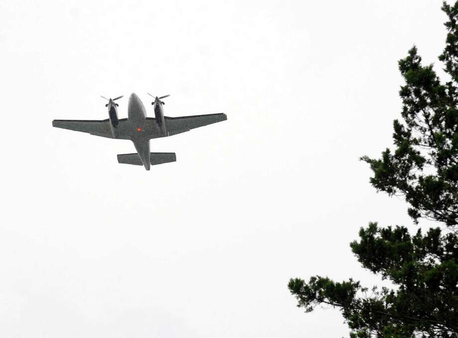 A double-engine propeller plane flies over the tree line above King Street in Greenwich, Conn., after taking off from Westchester County Airport in White Plains, N.Y., Friday afternoon, Aug. 1, 2014. Photo: Bob Luckey / Greenwich Time