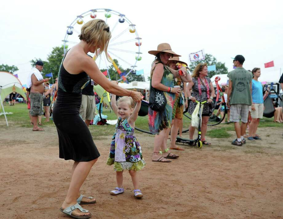 Kali Penders, of Madison, dances with 2-year-old daughter Rylee Friday, Aug. 1, 2014, at the annual Gathering of the Vibes music festival at Seaside Park in Bridgeport, Conn. Photo: Autumn Driscoll / Connecticut Post freelance