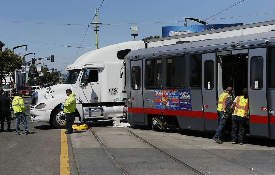A collision between a big rig truck and a MUNI light rail vehicle at the intersection of Innes and 3rd streets shut down both north and south bound lanes of 3rd street as emergency personnel responded to the scene in San Francisco, Calif. on Friday August 01, 2014. Photo: Michael Macor, The Chronicle