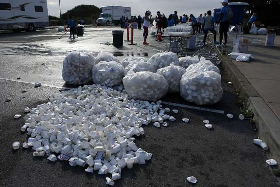 Used cups are cleaned up after runners in the San Francisco Marathon passed through the Vista Point turn around at the Golden Gate Bridge in San Francisco, Calif. on Sunday, July 27, 2014.