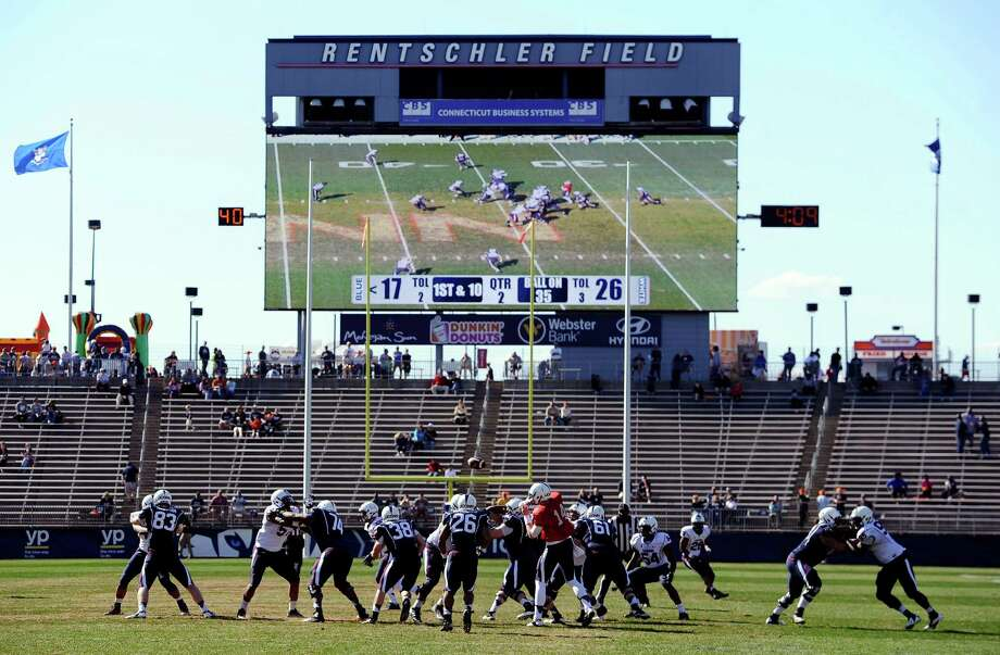 In this April 12, 2014 file photo Connecticut players run a play during the first half of UConn's Blue-White spring NCAA college football game at Rentschler Field, in East Hartford, Conn. Construction is nearly complete for UConn's new basketball training center in July 2014. In a series of projects designed to keep the school's athletic programs nationally competitive, the university has committed to building an on-campus hockey arena, and plans new facilities for soccer, baseball and softball. But athletic Director Warde Manuel said enlarging the 40,000-seat football stadium won't make sense until the school can sell the existing seats. (AP Photo/Jessica Hill, File) Photo: Jessica Hill, Associated Press / Associated Press