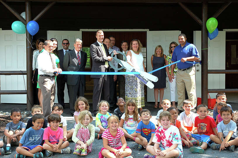 YMCA officials join children for a ribbon-cutting at Tuesday  for a new craft cabin at the YMCA Adve