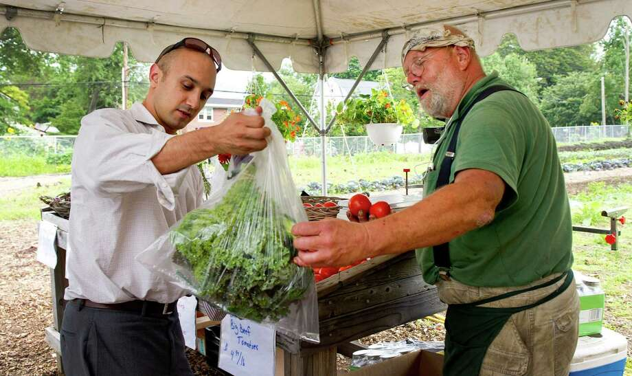 Ben Marcus, left, buys vegetables including kale, zucchini, onions and tomatoes from Randy Brown, right, at Hubbard Heights Farm in Stamford, Conn., on Friday, August 1, 2014. Photo: Lindsay Perry / Stamford Advocate