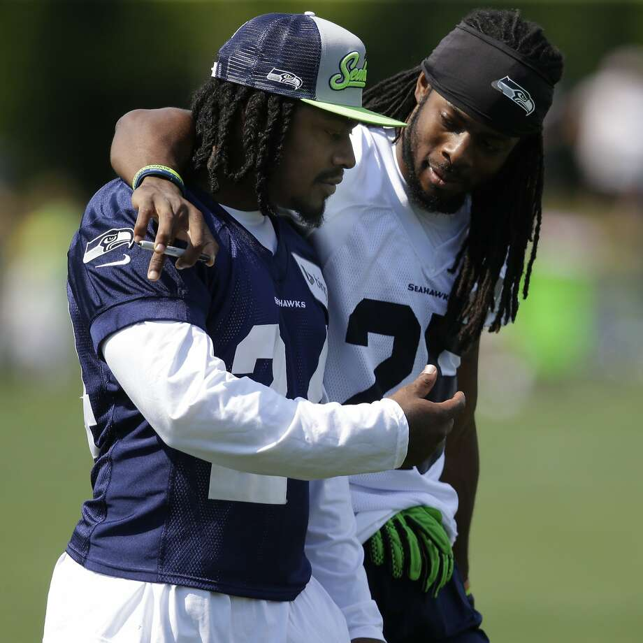Seattle's Marshawn Lynch (left) takes a stroll with Richard Sherman after the running back ended his holdout. Photo: Ted S. Warren, Associated Press