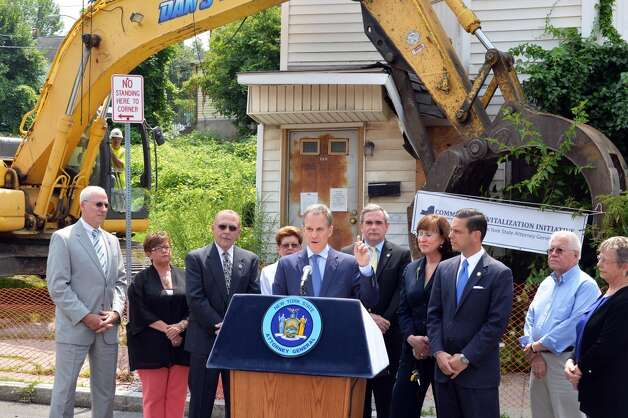 State Attorney General Eric Schneiderman, center, is joined by dignitaries as he announces a new round of funding for state land banks in front of 722 Eastern Ave. in Schenectady on Friday, Aug. 1, 2014.  (John Carl D'Annibale / Times Union) Photo: John Carl D'Annibale, Albany Times Union