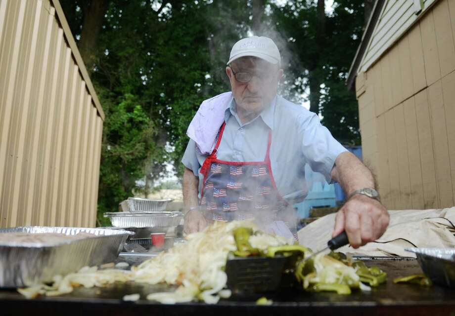 Vespucci Lodge member Mario Riccardi grills sausage, peppers and onions at the Amerigo Vespucci Annual Italian Festival at the Vespucci Lodge in Danbury, Conn. Friday, Aug. 1, 2014.  The festival features an array of authentic Italian food, live music, a classic car exhibit and many activities for children. Photo: Tyler Sizemore / The News-Times
