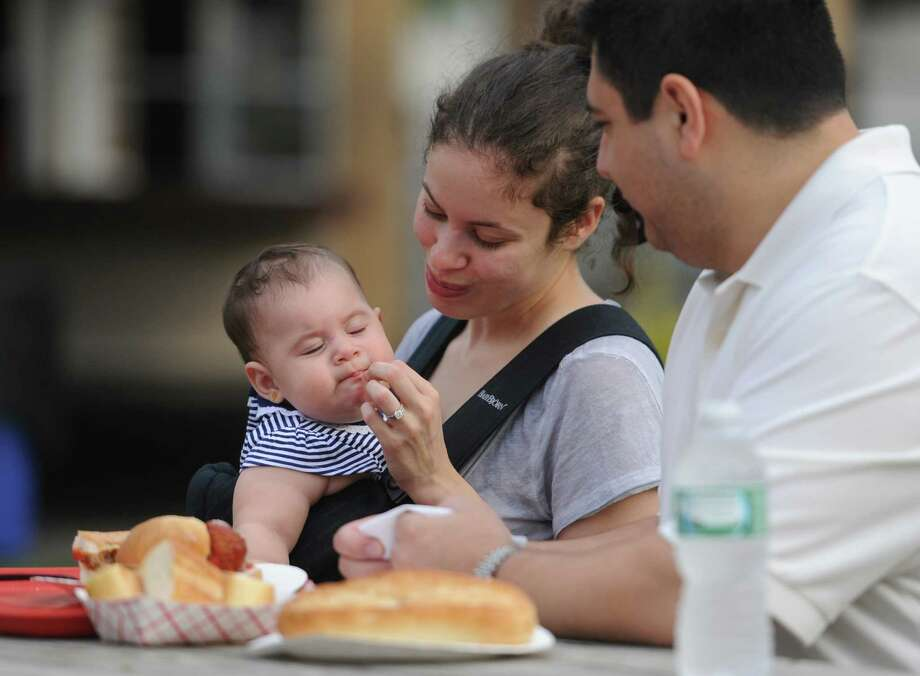 Nicole and Fernando Rivadeneira, of Ridgefield, feed their child Alessandra, 8 months, pieces of a meatball sub at the Amerigo Vespucci Annual Italian Festival at the Vespucci Lodge in Danbury, Conn. Friday, Aug. 1, 2014.  The festival features an array of authentic Italian food, live music, a classic car exhibit and many activities for children. Photo: Tyler Sizemore / The News-Times