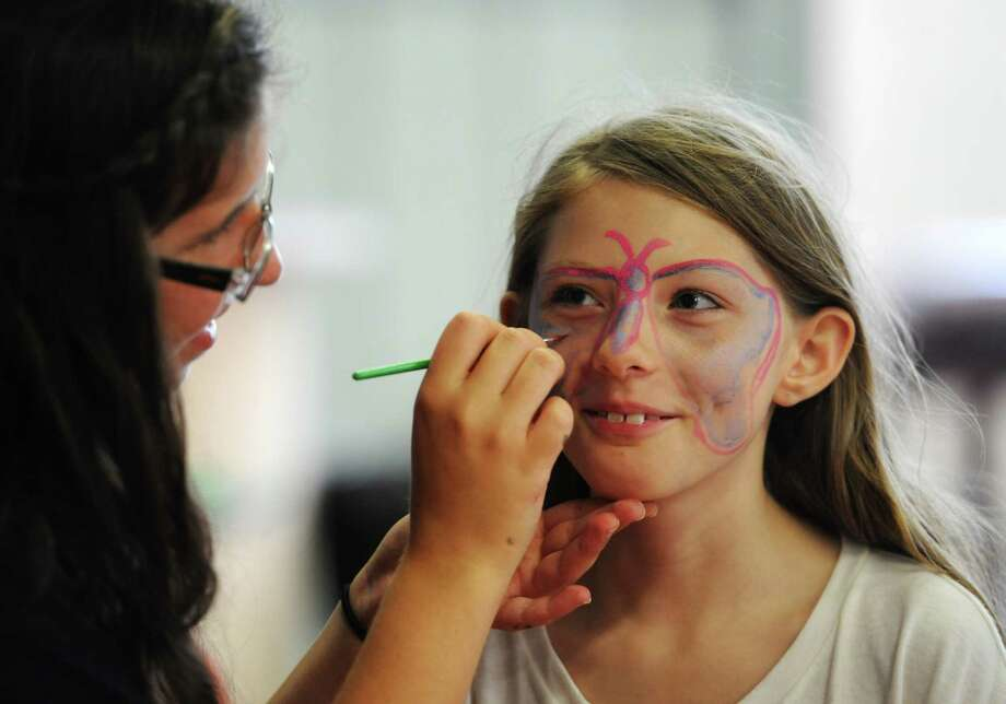 Lisa Grady, 11, of Danbury, gets her face painted by Gabriella Khoury, 17, of Danbury, at the Amerigo Vespucci Annual Italian Festival at the Vespucci Lodge in Danbury, Conn. Friday, Aug. 1, 2014.  The festival features an array of authentic Italian food, live music, a classic car exhibit and many activities for children. Photo: Tyler Sizemore / The News-Times