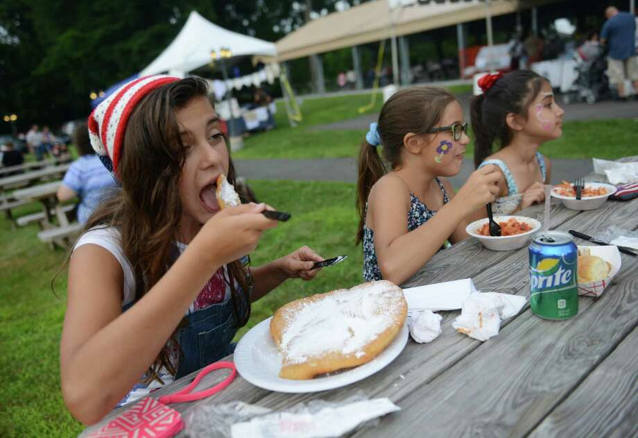 Gabriella Silva, left, 13, of Danbury enjoys fried dough with her sister Isabella Silva, center, 8, and Victoria Queiroz, 7, of Danbury at the Amerigo Vespucci Annual Italian Festival at the Vespucci Lodge in Danbury, Conn. Friday, Aug. 1, 2014.  The festival features an array of authentic Italian food, live music, a classic car exhibit and many activities for children. Photo: Tyler Sizemore / The News-Times