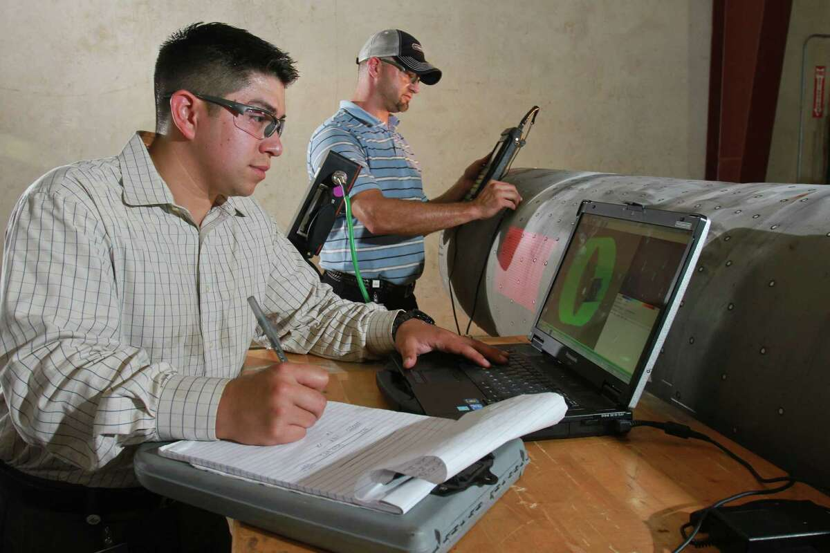 Steven Trevino, left, and Jason James perform anomaly characterization using multiple non-destructive examination techniques on a section of pipeline. Steven is program manager for the Pipeline Research Council International, Inc. (For the Chronicle/Gary Fountain, July 24, 2014)