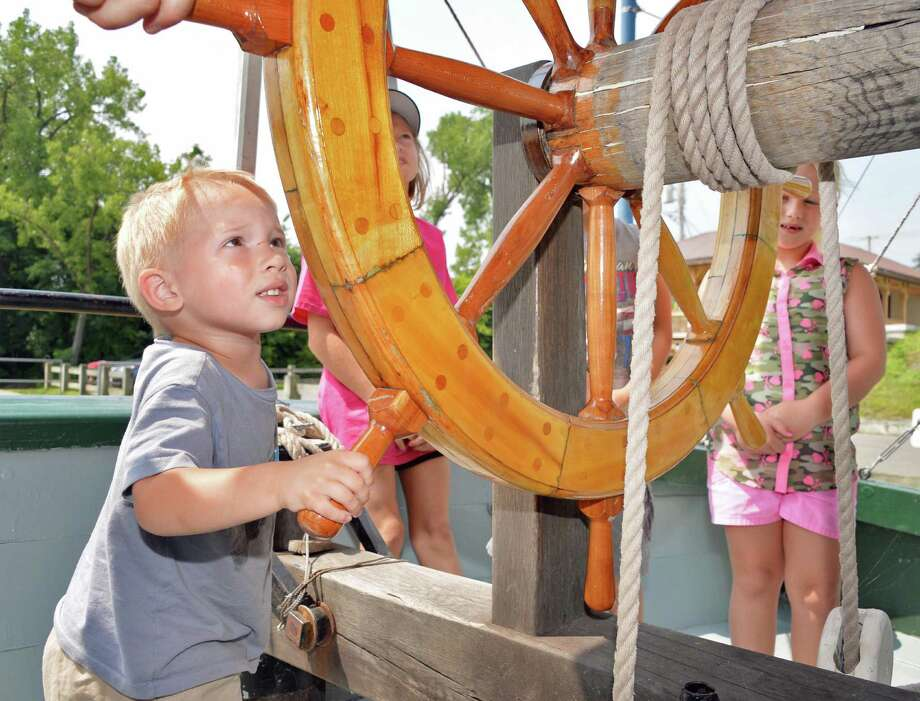 Three-year-old Chase Lucarelli of Schagticoke gets to try his hand at the helm of the Lake Champlain Maritime Museum's Schooner Lois McClure during its visit Friday August 1, 2014, in Mechanicville, NY.  (John Carl D'Annibale / Times Union) Photo: John Carl D'Annibale / 00028007A