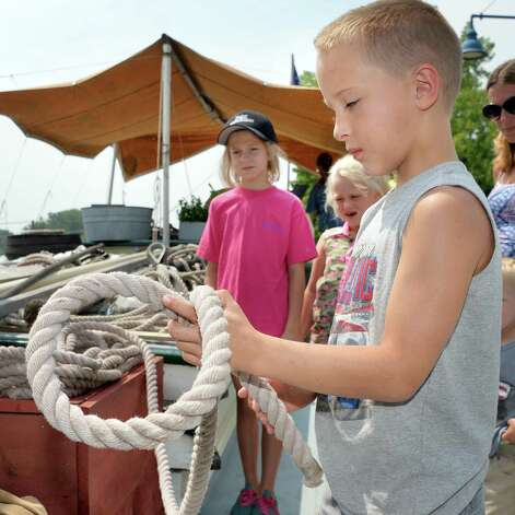 Ethan Burke, 9, of Schaghticoke knots a line on the deck of the Lake Champlain Maritime Museum's Schooner Lois McClure during its visit Friday August 1, 2014, in Mechanicville, NY.  (John Carl D'Annibale / Times Union) Photo: John Carl D'Annibale / 00028007A