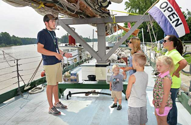 Crew member Isaac Parker, 18, left, welcomes visitors aboard the Lake Champlain Maritime Museum's Schooner Lois McClure during its visit Friday August 1, 2014, in Mechanicville, N.Y.  (John Carl D'Annibale / Times Union) Photo: John Carl D'Annibale / 00028007A