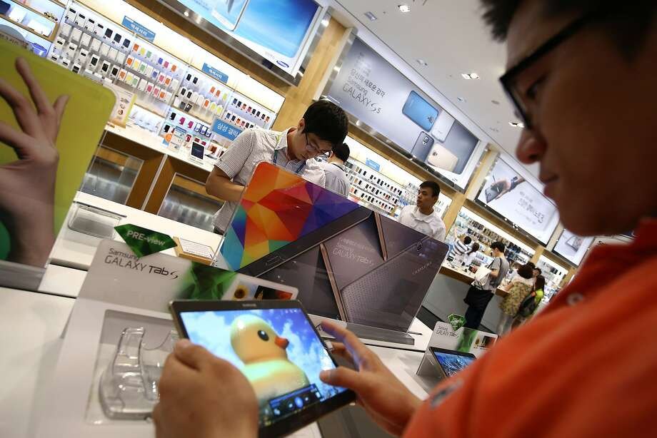 Customers try out Samsung Galaxy Tab S tablet computers at the company's store in Seoul last month. Sales of tablets have slowed, affecting makers of the devices and suppliers of parts. Photo: SeongJoon Cho, Bloomberg