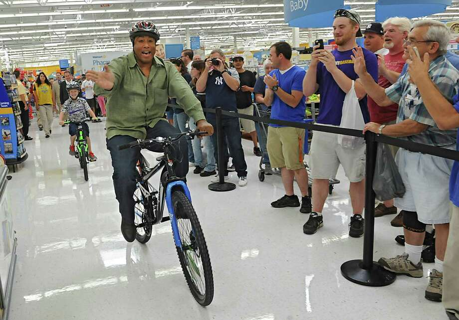 Ballston Spa 9-year-old Nick Rychcik and four-time World Series champion Bernie Williams of the New York Yankees ride bikes through the Walmart Supercenter on Friday, Aug. 1, 2014, in Glenmont, N.Y. Fans are lined up at right to get an autograph from Williams after the shopping spree. Nick had a $100 shopping spree with the baseball legend. The event is part of a program called Shop with a MLB Player sponsored by PepsiCo. Rychcik, a childhood cancer patient at Albany Med's Melodies Center for Childhood Cancer and Blood Disorders and is a huge baseball fan. (Lori Van Buren / Times Union) Photo: Lori Van Buren / 00028015A
