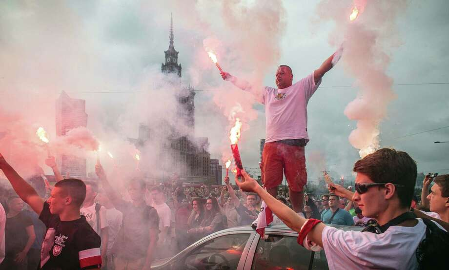 Warsaw residents stand still and hold burning flares to pay tribute to the Polish fighters who battled Nazi German occupation troops in 1944. Photo: WOJTEK RADWANSKI, AFP/Getty Images / AFP