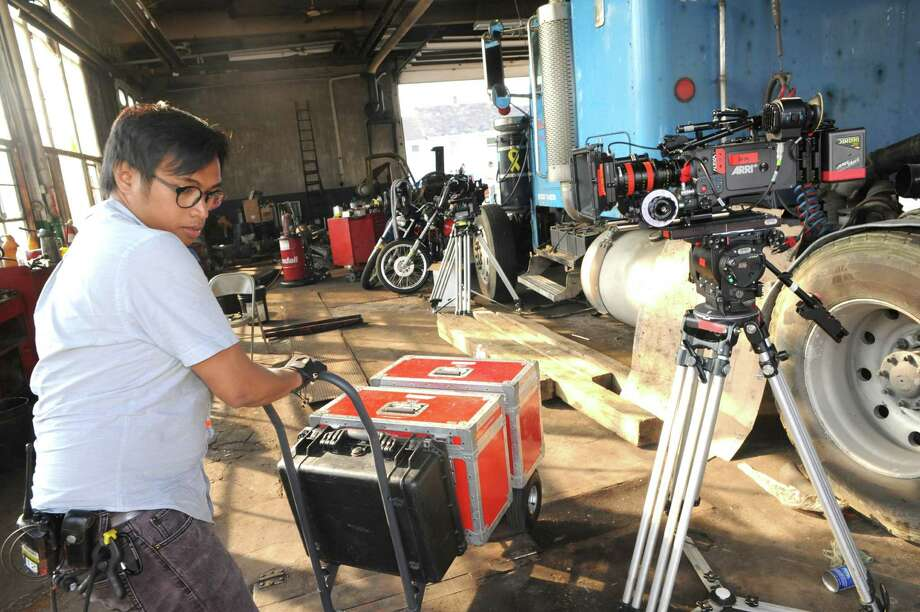 """Assistant cameraman Jae Mal packs up equipment following a shoot at J.A. Sweet Trucking during filming of the movie """"Kill for Me"""" on Thursday July 31, 2014 in Amsterdam, N.Y. (Michael P. Farrell/Times Union) Photo: Michael P. Farrell / 00028023A"""