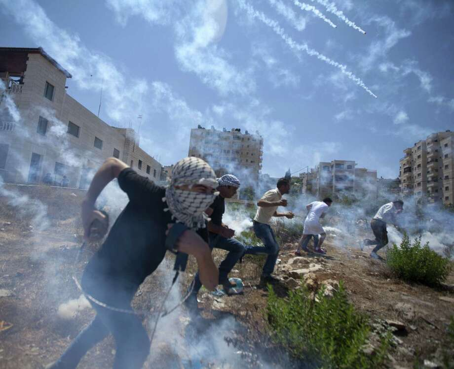 Palestinians run for cover during clashes with Israeli soldiers following a protest against the war in the Gaza Strip, outside Ofer, an Israeli military prison near the West Bank city of Ramallah. Photo: Lefteris Pitarakis / Associated Press / AP
