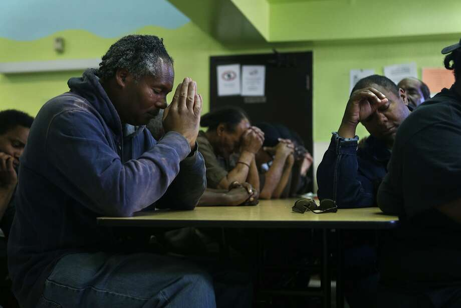 Phillip House (left) and Richard Lofton pray before dinner at Mother Brown's Kitchen next to the proposed shelter site. Photo: Scott Strazzante, The Chronicle