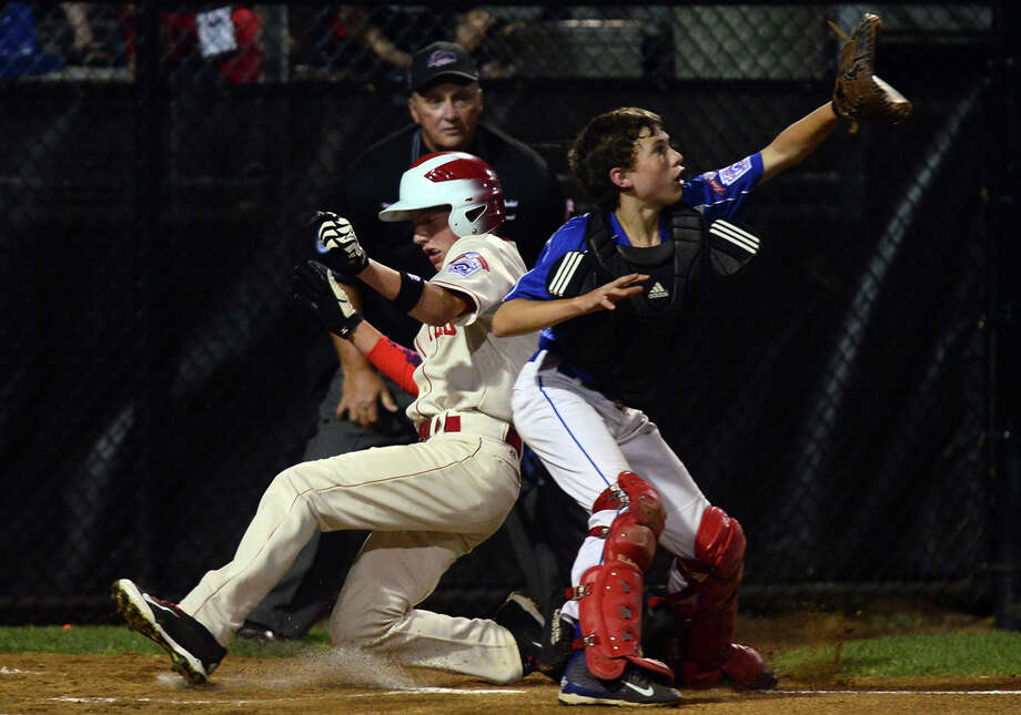 Connecticut's Brian Howell slides into home plate as Vermont catcher Jonah Roberts waits for the ball during New England tournamnent action at Breen Field in Bristol, Conn. on Friday August 1, 2014. Photo: Christian Abraham / Connecticut Post