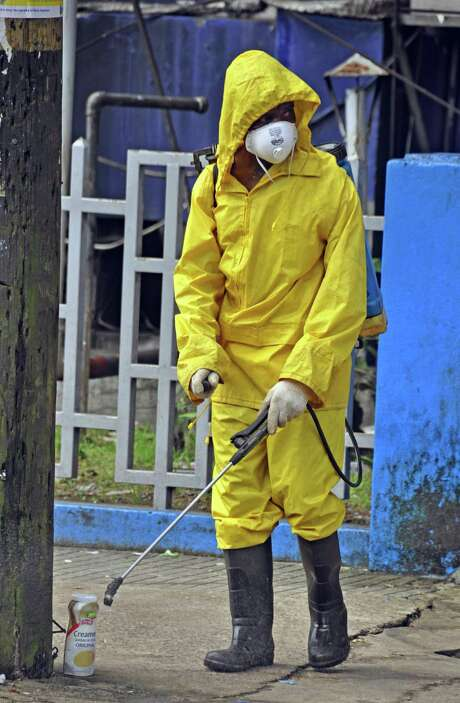 A city employee in Monrovia, Liberia, sprays disinfectant in a bid to prevent the spread of the Ebola virus that has killed hundreds in West Africa. Photo: Photos By Abbas Dulleh / Associated Press / AP