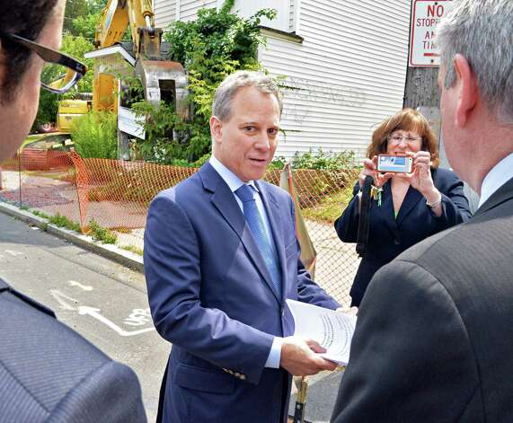 State Attorney General Eric Schneiderman, center, arrives for an  announcement about a new round of funding for NYS land banks as Amsterdam Mayor Ann Thane snaps his photo Friday, August 1, 2014, in Schenectady, N.Y. (John Carl D'Annibale / Times Union) Photo: John Carl D'Annibale / 00028032A