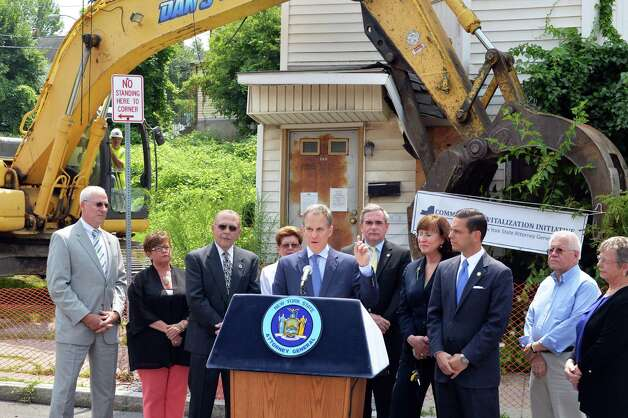 State Attorney General Eric Schneiderman, center, is joined by dignitaries as he announces a new round of funding for NYS land banks in front of 722 Eastern Ave. Friday, August 1, 2014, in Schenectady, N.Y. (John Carl D'Annibale / Times Union) Photo: John Carl D'Annibale / 00028032A