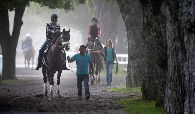 Fog shrouds the walkway near the main track as horses return from their morning exercise at the Saratoga Race Course early Friday morning Aug. 1, 2014 in Saratoga Springs, N.Y.    (Skip Dickstein photos Photo: SKIP DICKSTEIN