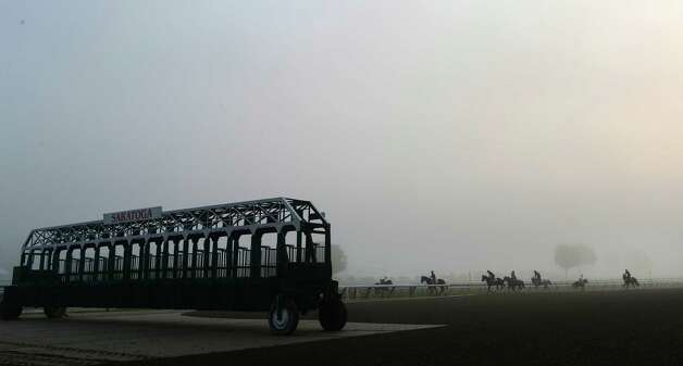 Fog shrouds the main track as horses go out for their morning exercise at the Saratoga Race Course early Friday morning Aug. 1, 2014 in Saratoga Springs, N.Y.    (Skip Dickstein photos Photo: SKIP DICKSTEIN