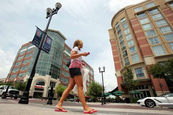 A pedestrians move about at lunch time at the Sugar Land Town Square on Thursday, July 31, 2014, in Sugar Land.