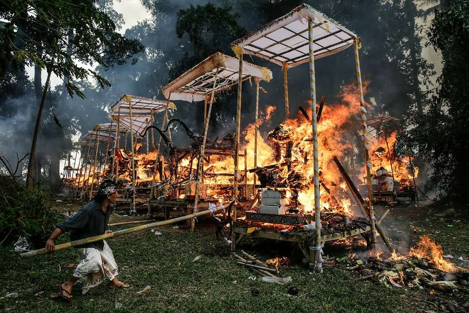 UBUD, BALI, INDONESIA - AUGUST 01:   A Balinese man burns a sarcophagus in the shape of buffalo during Balinese Hindu mass cremation on August 1, 2014 in Ubud, Bali, Indonesia. More than 100 corpses were collectively cremated in the ceremony known as Ngaben Masal (Mass Cremation). Taking place every 4 years in Singakerta Village, it is one of the most important ceremonies for Balinese Hindu people. They believe during the burnings, that deceased bodys spirit will be freed to reincarnate. (Photo by Agung Parameswara/Getty Images) *** BESTPIX *** Photo: Agung Parameswara, Getty Images