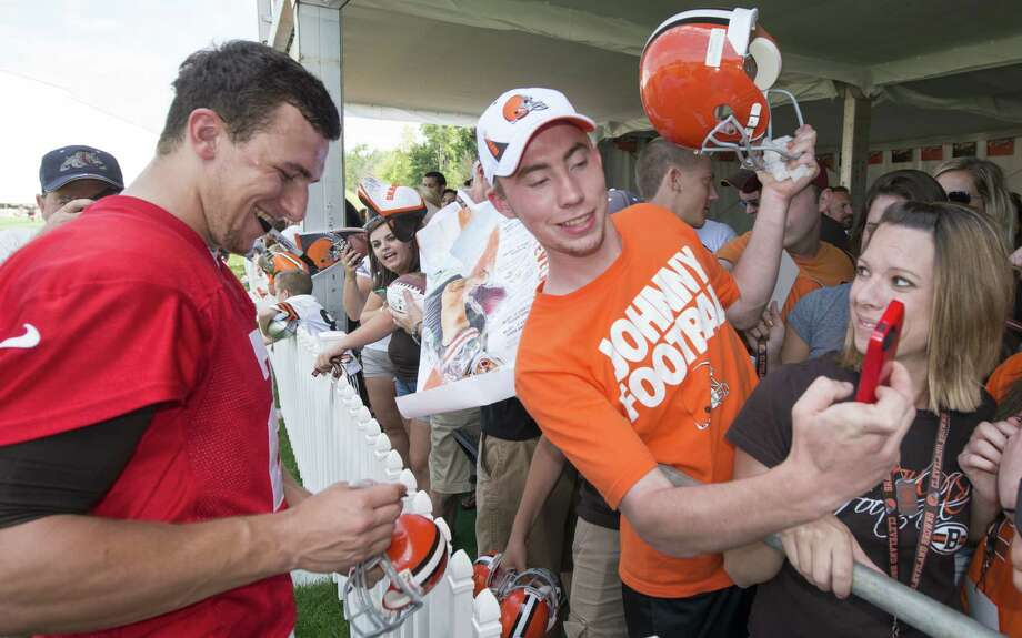 Quarterback Johnny Manziel signs autographs as a fan takes a selfie during training camp in Berea, Ohio. Photo: Jason Miller / Getty Images / 2014 Getty Images