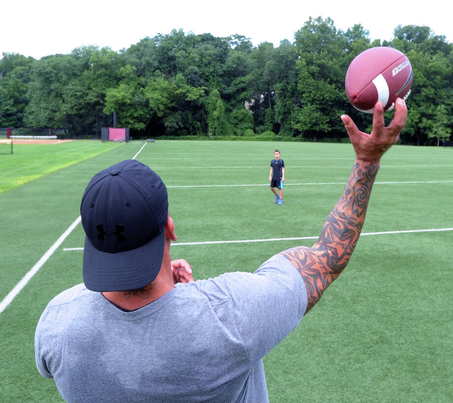 Foreground, Joe Mecca of Greenwich has a football catch with his son, Joey, 10, on the football field at Greenwich High School, Saturday morning, Aug. 2, 2014. The younger Mecca said he will be playing quaterback for a team in a  Rye, N.Y., youth football league and was practicing roll-out passing with the help of his father. Photo: Bob Luckey / Greenwich Time