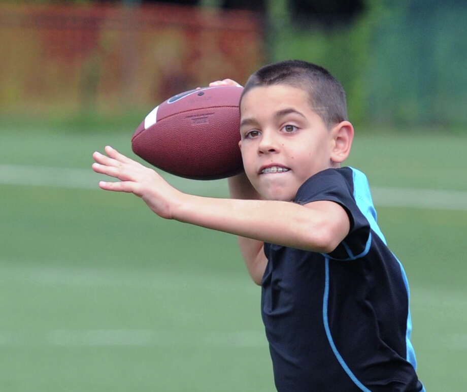 Joey Mecca, 10, of Greenwich, has a football catch with his dad, Joe Mecca, on the football field at Greenwich High School, Saturday morning, Aug. 2, 2014. The younger Mecca said he will be playing quaterback for a team in a  Rye, N.Y., youth football league and was practicing roll-out passing with the help of his father. Photo: Bob Luckey / Greenwich Time