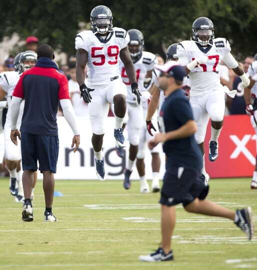 Texans outside linebackers Whitney Mercilus (59) and Justin Tuggle (57) leap into the air during war
