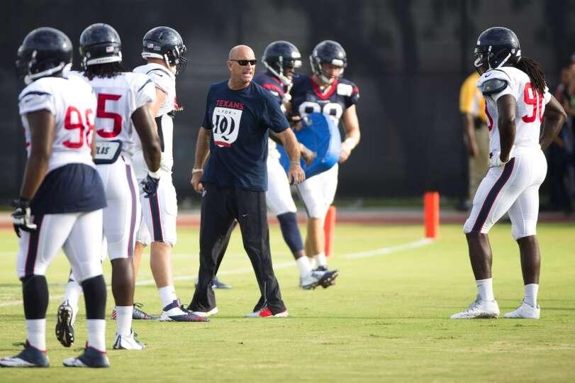 Texans defensive line coach Bill Kollar works with linebacker Jadeveon Clowney (90).