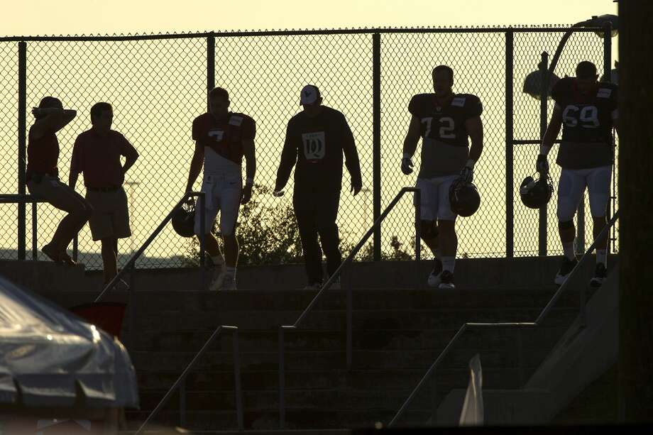 Day 7: August 2   Texans players and coaches are silhouetted as the sun rises behind them as they walk to practice. Photo: Brett Coomer, Houston Chronicle