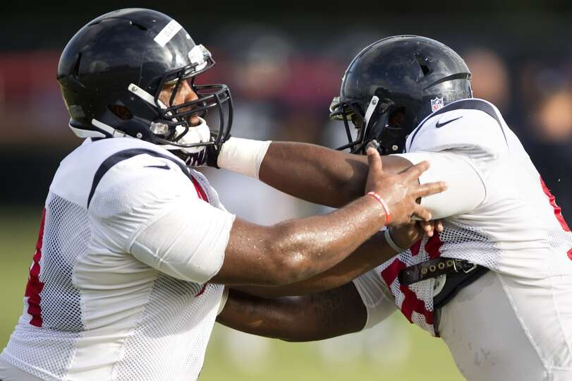 Texans defensive ends Julius Warmsley, left, and Jeoffrey Pagan run through a pass rush drill.