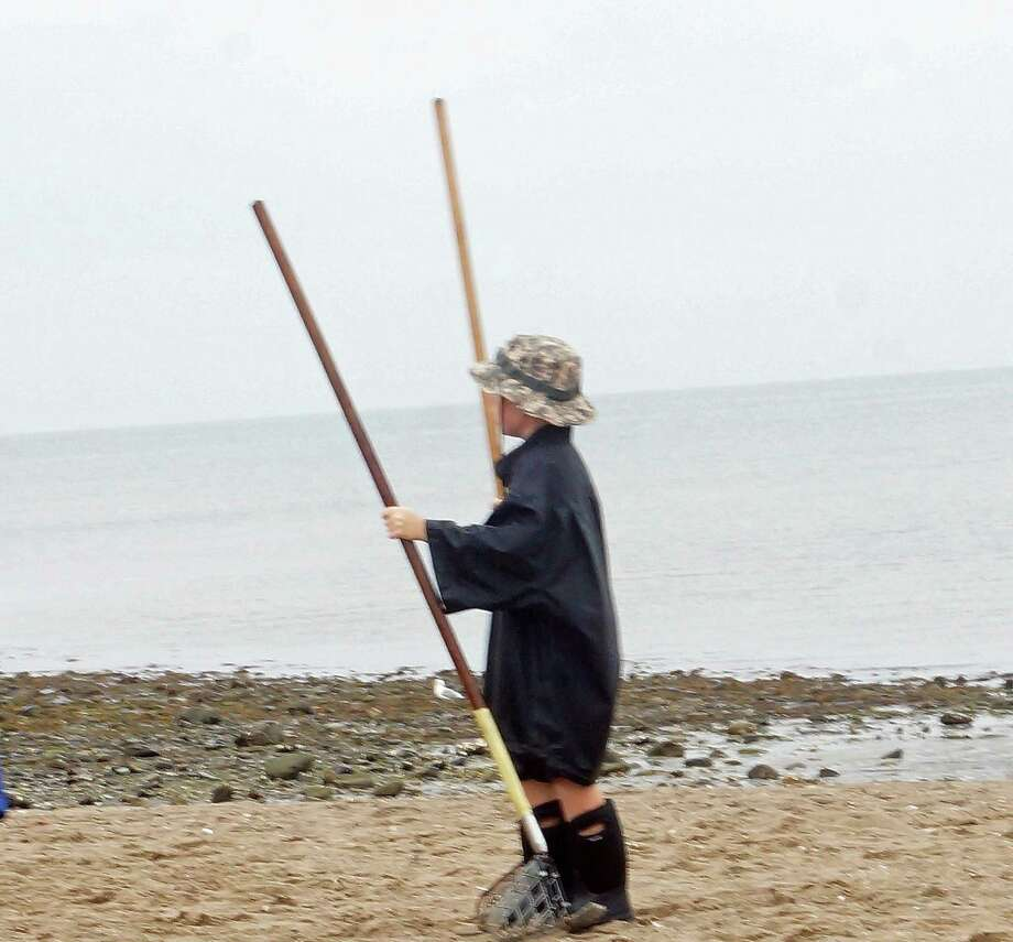 A young clammer grabs some rakes at a clam clinic Saturday at Sasco Beach, hosted by the Shellfish Commission. Photo: Genevieve Reilly / Fairfield Citizen