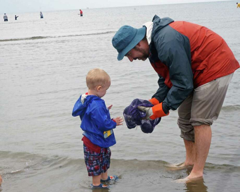 Adam Rosen shows off his clam catch to Grant Ferrari, the almost two-year-old son of Shellfish Commission member Ricky Ferrari at the clam clinic Saturday. Photo: Genevieve Reilly / Fairfield Citizen