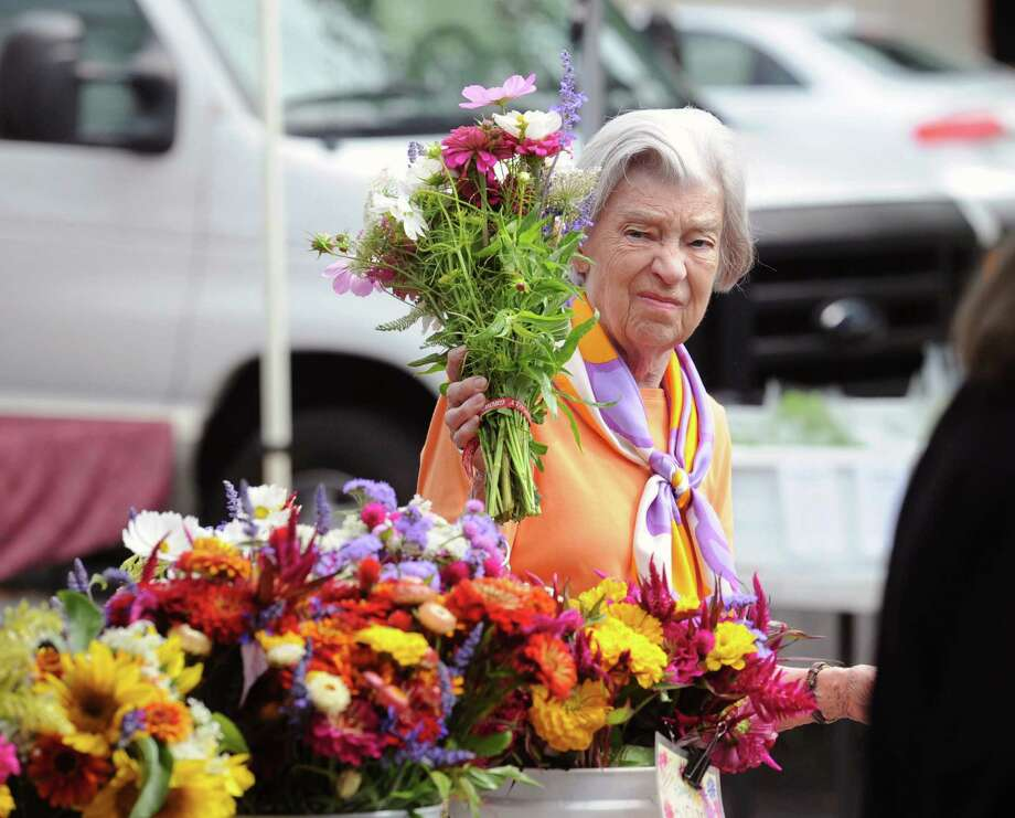 Jean MacFarlane of Greenwich buys a bouquet of flowers at the Riverbank Farm (Roxbury, Conn.) stand during the Greenwich Farmers Market in the Horseneck public parking lot across the street from the Boys & Girls Club in Greenwich, Conn., Saturday morning, Aug. 2, 2014. The market is open on Saturdays 9:30am to 1:00pm at the lot and runs until November. Photo: Bob Luckey / Greenwich Time