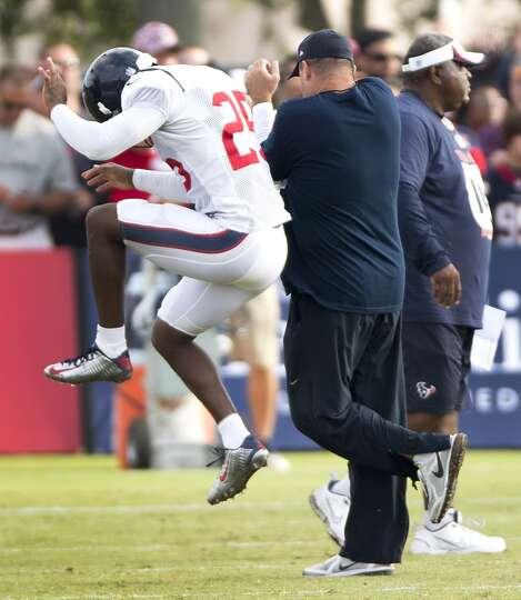 Texans cornerback Kareem Jackson (25) leaps up and bumps head coach Bill O'Brien.