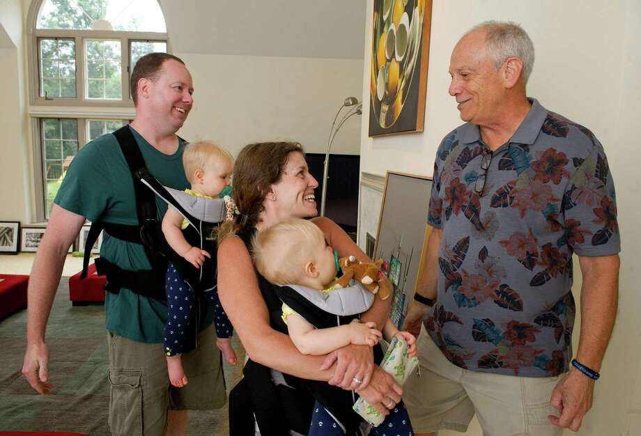 Nancy and Michael O'Farrell carry their twin 10-month-old daughters, Kayleigh, left, and Finley, right, as they say hello to Rick Lundt during Lundt's estate sale on Saturday, August 2, 2014. The O'Farrell family recently purchased the Emerald Lane home from Lundt. Photo: Lindsay Perry / Stamford Advocate