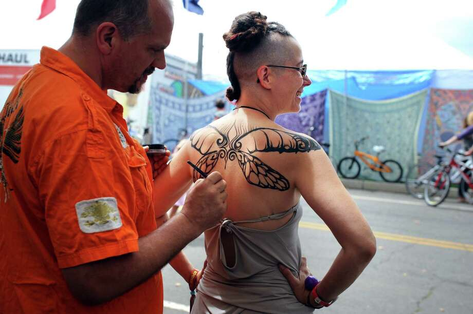 Artist Vann Godfrey paints wings on the back of Emily Sparkle, of East Hampton, Mass., in the Body Arts Booth at the annual Gathering of the Vibes music festival Saturday, Aug. 2, 2014, at Seaside Park in Bridgeport, Conn. Photo: Autumn Driscoll / Connecticut Post freelance